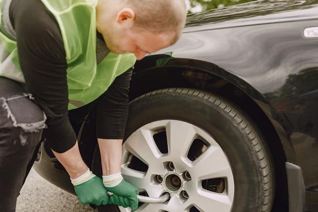 Man changing broken wheel on car Free Photo