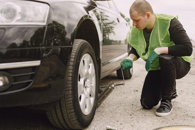 Человек меняет сломанное колесо на автомобиле Бесплатные Фотографии