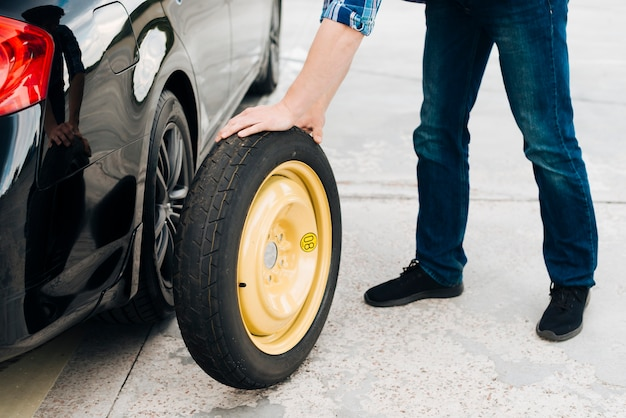 Man changing car tire with spare tire Free Photo