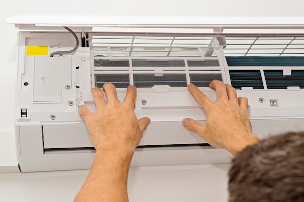Man changing the filter in the air conditioning Premium Photo