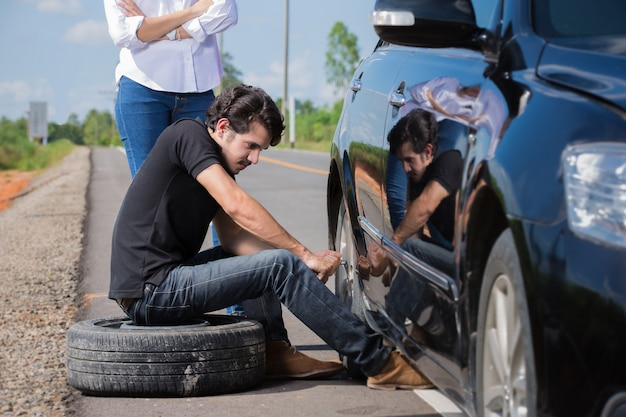 Man changing tire that are leaking his car broke down Premium Photo