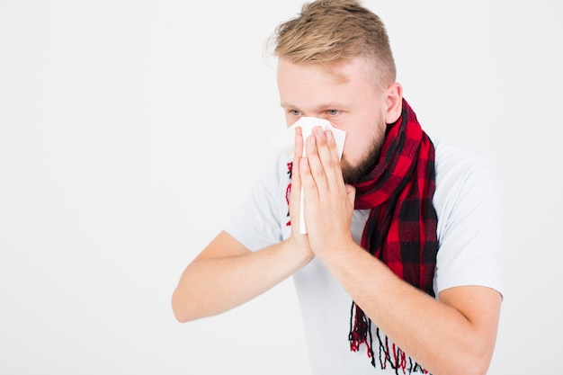 Man in checkered scarf blowing nose Free Photo