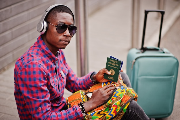 Man in checkered shirt, sunglasses and earphones with suitcase and backpack holding ghana passport Premium Photo