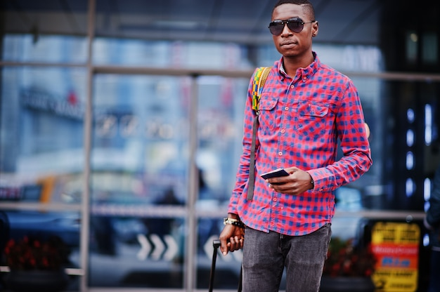 Man in checkered shirt, with suitcase and backpack Premium Photo
