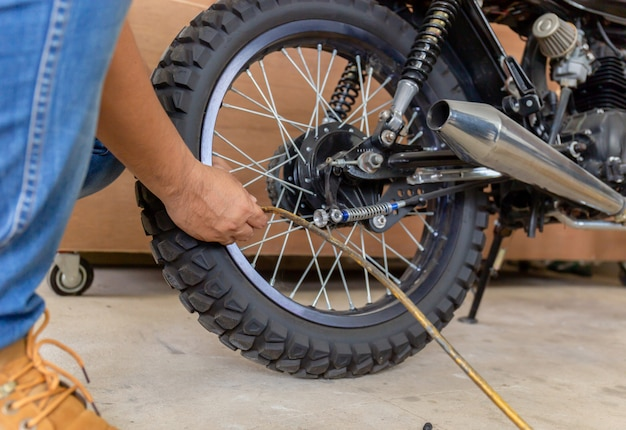 Man checking air pressure and filling air in the motorcycle tires Premium Photo