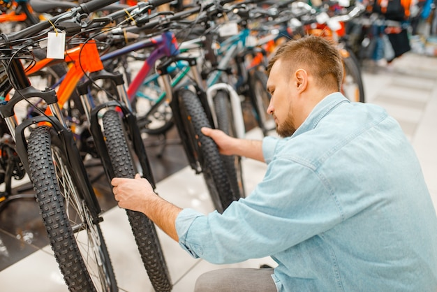 Человек проверяет велосипедную шину, делая покупки в спортивном магазине Premium Фотографии
