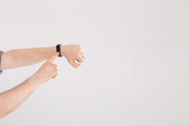 Человек проверяет пульс на фитнес-браслете или шагомере трекера активности на запястье Premium Фотографии