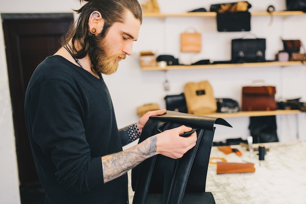 Man checks for quality leather backpack. Free Photo