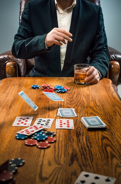 The man, chips for gamblings, drink and playing cards Free Photo