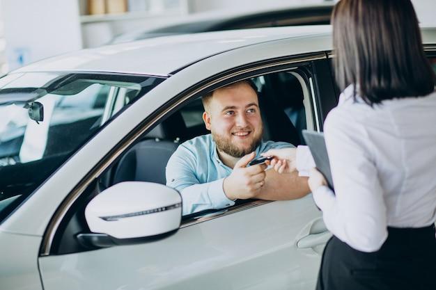 자동차 살롱에서 차를 선택하는 남자 무료 사진