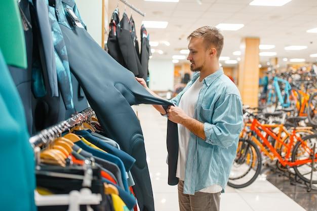 Мужчина выбирает велосипедный костюм, делая покупки в спортивном магазине. Premium Фотографии