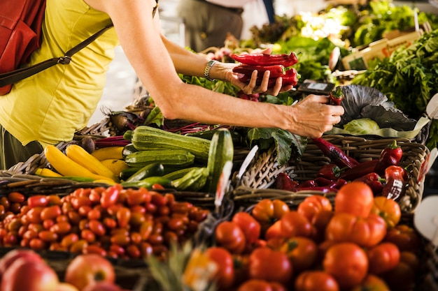 Man choosing vegetable from vegetable stall at supermarket Free Photo