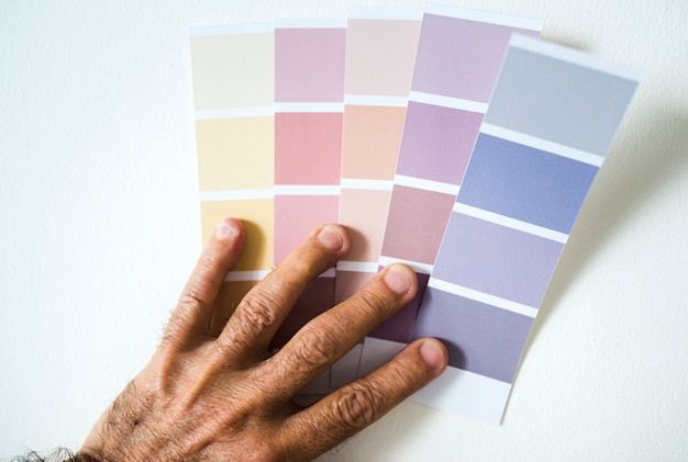 Man choosing wall color by choosing from a color swatch Free Photo