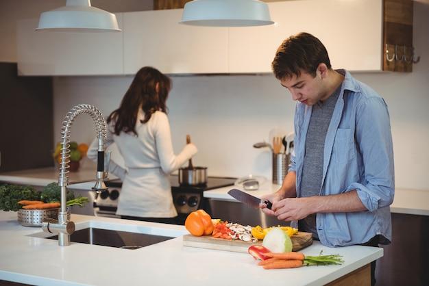 Мужчина нарезает овощи на кухне, пока женщина готовит еду в фоновом режиме Бесплатные Фотографии