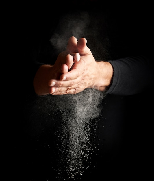 Man claps his hands and scatters to the side a white substance on a black background Premium Photo