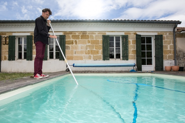 Man cleaning blue swimming pool with vacuum cleaner Photo ...