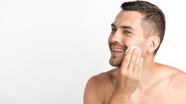 白い背景の上に綿のパッドをバッティングで顔の皮膚をクリーニング男 Premium写真