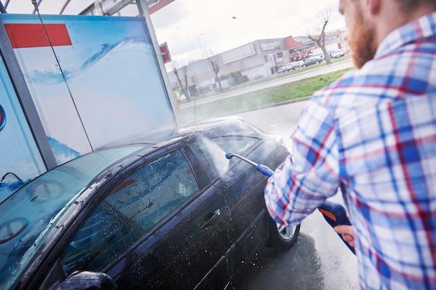 セルフサービスで車を掃除している男性 無料写真