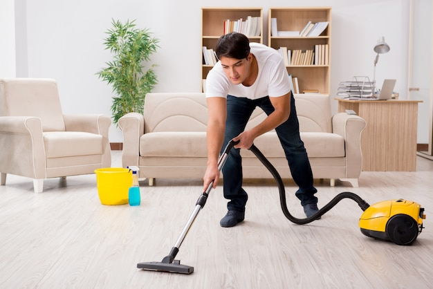 Man cleaning home with vacuum cleaner Premium Photo
