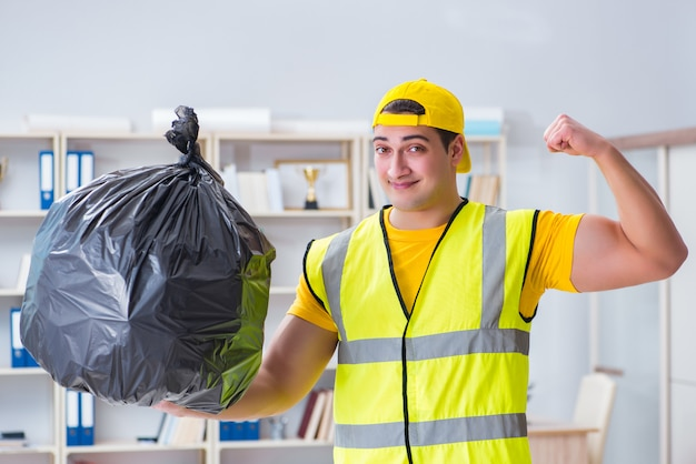 Man cleaning the office and holding garbage bag Premium Photo