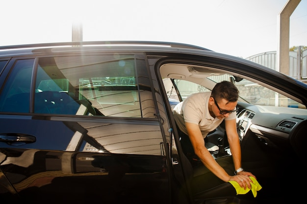 Man cleaning a seat of a black car Free Photo