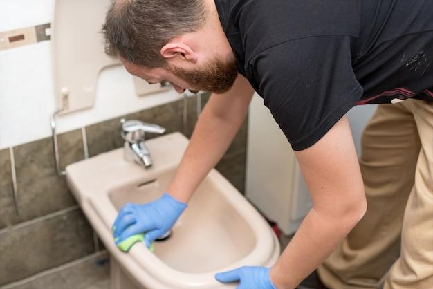 Man cleaning toilet bidet Premium Photo