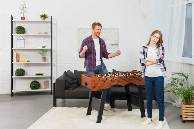 Man clenching her fist with joy looking at sad woman in the modern living room Free Photo