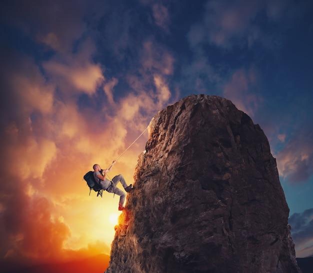 Человек поднялся на гору, чтобы получить флаг. цель достижения и сложная концепция карьеры Premium Фотографии