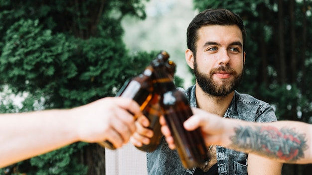 Man clinking beer bottles with his friends Free Photo