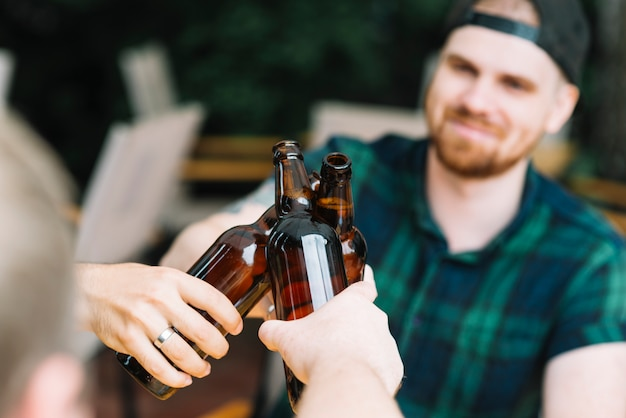 Man clinking the glass bottles of beer with friends Free Photo