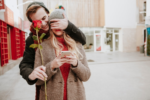 Man closing eyes to girlfriend and giving rose Free Photo