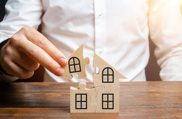 A man collects a house of puzzles. construction of your own residential building. mortgage loan Premium Photo