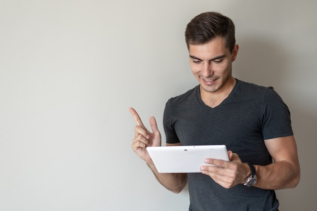 Man for conceptual. handsome young man uses a tablet standing at a gray wall, copy space Premium Photo