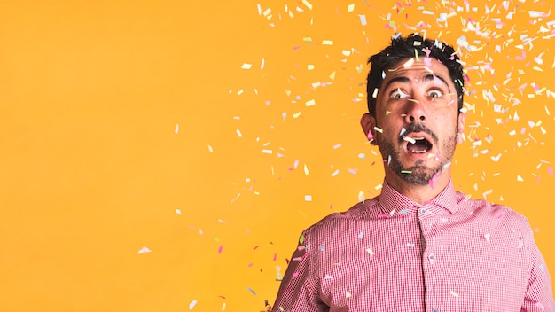 Man and confetti on orange background with copy space Free Photo