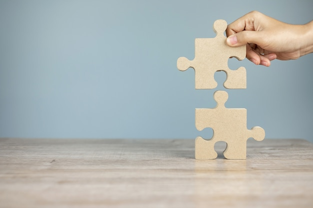 Man connecting couple puzzle piece, wood jigsaw on table  . business solutions, mission, success, goals and strategy concepts Premium Photo