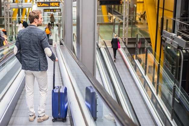 Man on the conveyor escalator at the airport Premium Photo