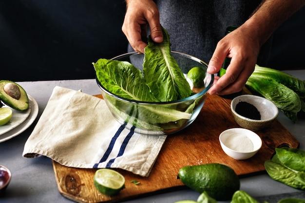 Man cooking green detox salad romaine lettuce healthy food Premium Photo