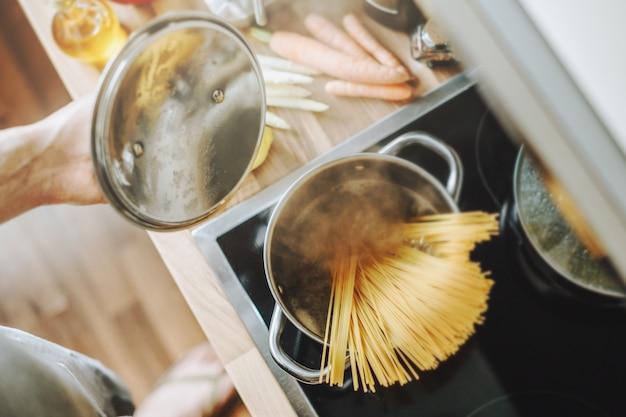 男は自宅のキッチンでパスタスパゲッティを調理します。家庭料理やイタリア料理のコンセプト。 無料写真