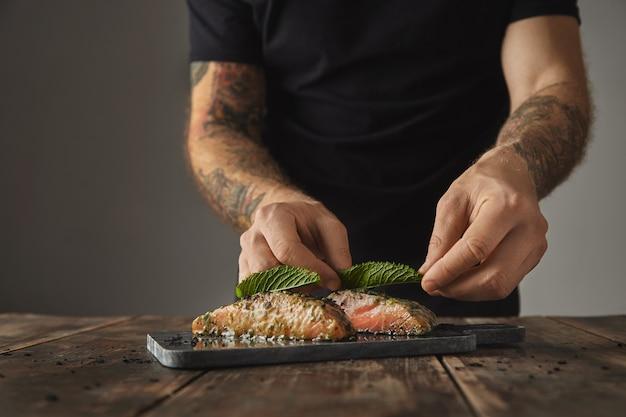 Мужчина готовит здоровую еду на деревенском столе, украшает листом мяты два сырых кусочка лосося в соусе из белого вина со специями и травами, представленными на мраморной палубе, приготовленной для гриля Бесплатные Фотографии