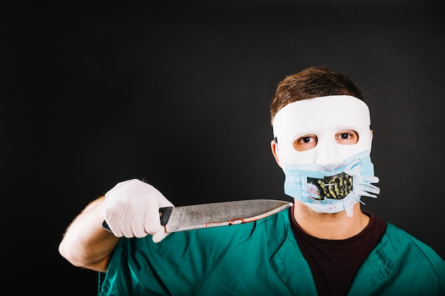 Man in costume threatening with knife Free Photo