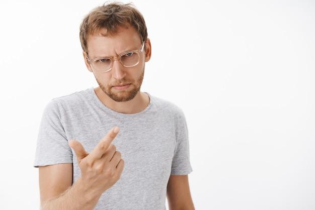 Uomo che conta quante volte il dipendente sbaglia sentendosi incazzato e infastidito volendo fuoco povero ragazzo guardando da sotto la fronte con sguardo arrabbiato pericoloso che fa il gesto della pistola del dito sopra il muro bianco Foto Gratuite