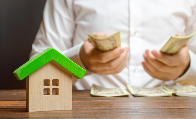 A man counts money on the of the figures of the house. calculation of property tax Premium Photo