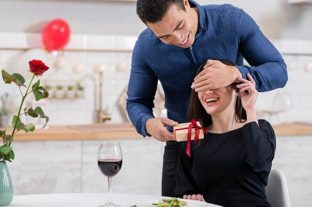 Man covering his girlfriend's eyes before giving her a gift Free Photo