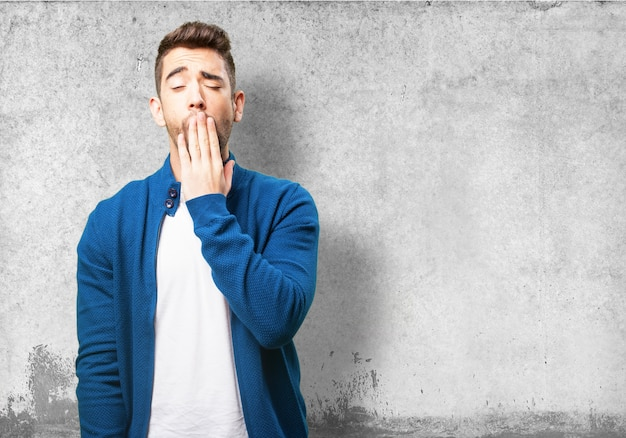 Man covering his mouth while yawning Free Photo