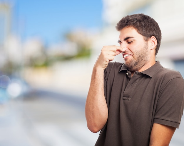Man covering his nose with disgust Free Photo