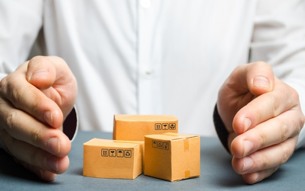 Man covers his hands with cardboard boxes or goods Premium Photo