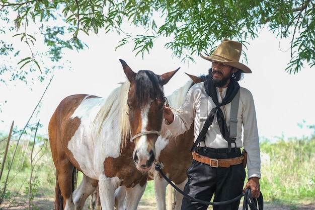 A man in a cowboy outfit with his horse Premium Photo