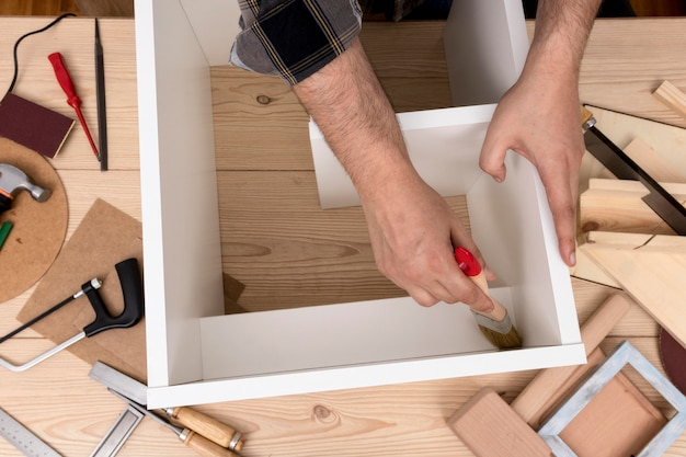Man creating a cabinet from wood top view Premium Photo