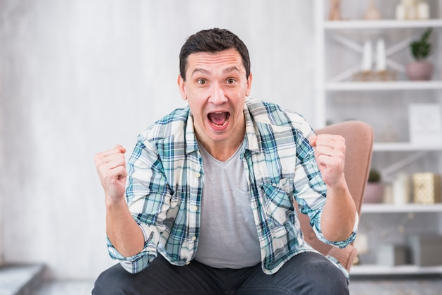 Man crying and showing fists on chair at home Free Photo