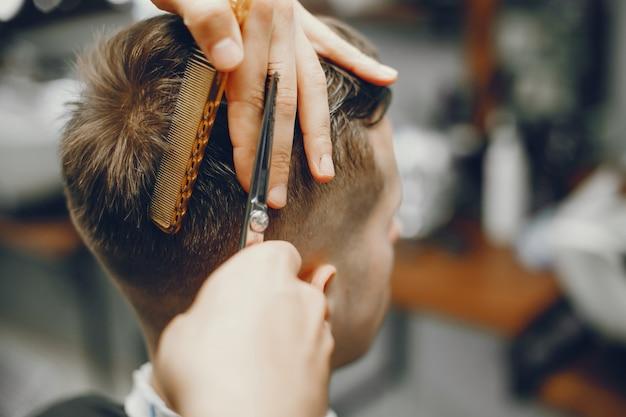 Un uomo taglia i capelli in un negozio di barbiere Foto Gratuite